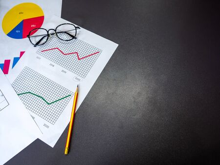 Business goal concept. Top view of business accessory, diagrams graphs, pencil and glasses on dark table with copy space.