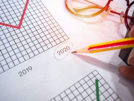 Business goal concept. Close-up hand pointing 2020 on diagrams graphs by pencil and glasses on table.