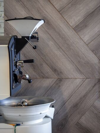 Coffee roaster on wooden wall background with copy space vertical style. Фото со стока