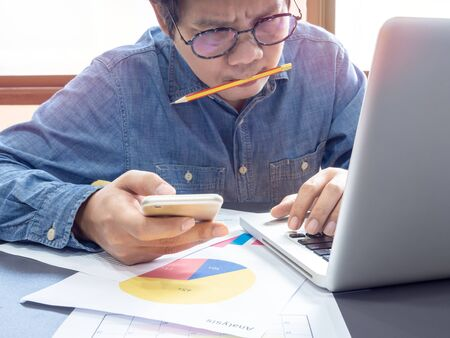 Asian businessman wearing blue shirt and glasses holding smartphone and pencil in his mouth feel strain with working with laptop computer on table near the window in office.