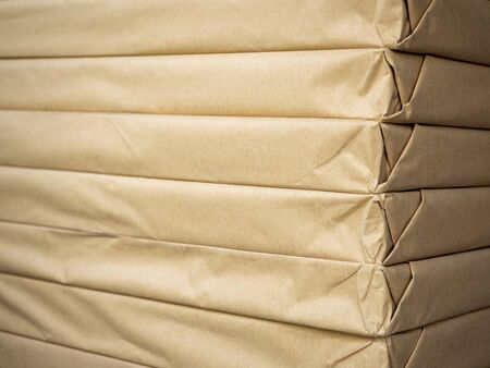 Stack of brown paper packaging. Close-up side of corner of wrapping packaging.