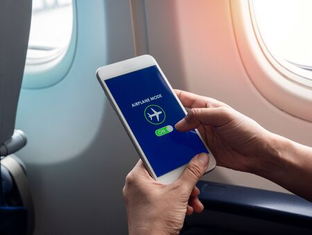 Flight mode concept. Finger sliding on screen for turned on airplane mode near the window on the airplane. Archivio Fotografico