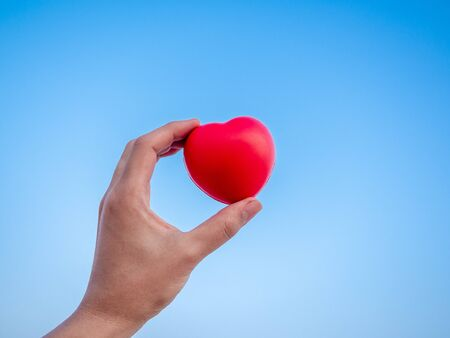 Red heart in hand on blue sky background, love, peace and giving concept.