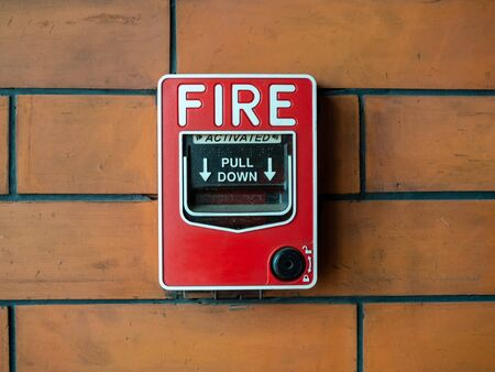 Red manual pull fire alarm safety system. Close-up pull station or call point, manual fire alarm activation on brick wall background.