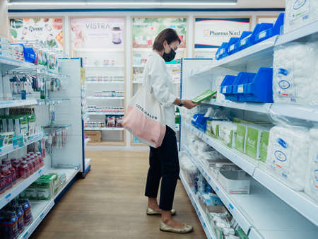 Bangkok, Thailand - March 25, 2020: Asian woman wearing protective face mask looking medical productin pharmacy store in Bangkok, Thailand.