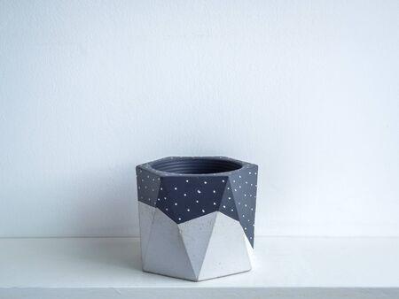 Cactus pot. Concrete pot. Empty grey painted modern geometric concrete planter on white wooden shelf isolated on white background.