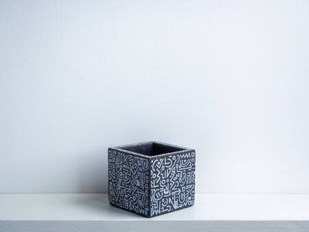 Cactus pot. Concrete pot. Empty black with modern graphic pattern geometric concrete planter on white wooden shelf isolated on white wall background.