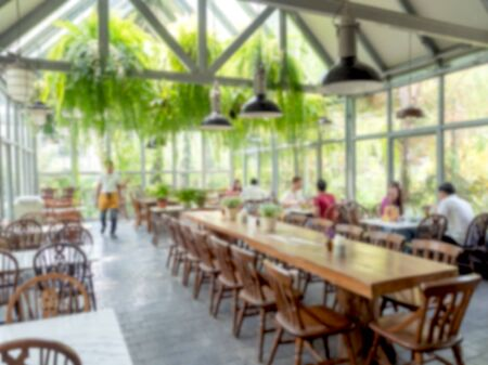 Burred restaurant background. Interior cafe decoration with hanging green natural plants, wooden table and people in glasshouse building.