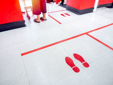 Red footprint and red line on floor in supermarket for warning for keep a safe social distance protect from Coronavirus, social distancing concept.