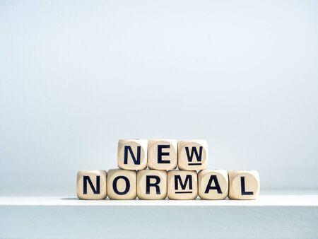 Close-up New Normal, mots sur cube alphabet en bois sur étagère sur fond blanc. Nouvelle normalité après le concept de pandémie de covid-19.