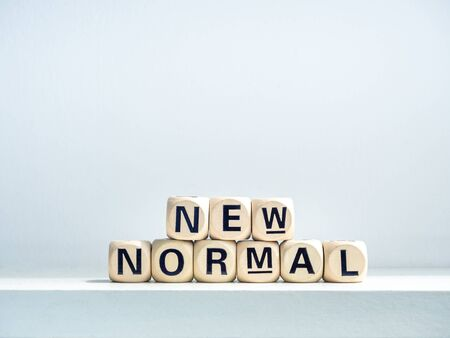 Close-up New Normal, words on wooden alphabet cube on shelf on white background. New normal after covid-19 pandemic concept.