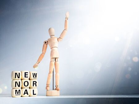 New Normal, words on wooden alphabet cube and wooden figure raising up hand with sparkle shining light with copy space. New normal life after covid-19 pandemic concept.