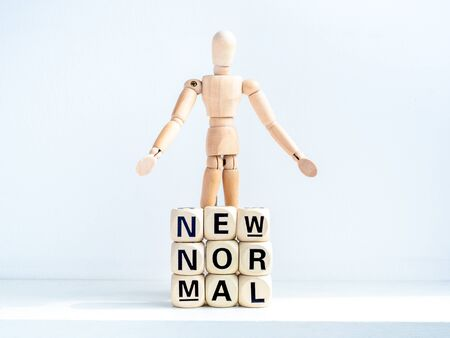 New Normal, words on wooden alphabet cube and wooden figure on white background. New normal life after covid-19 pandemic concept.