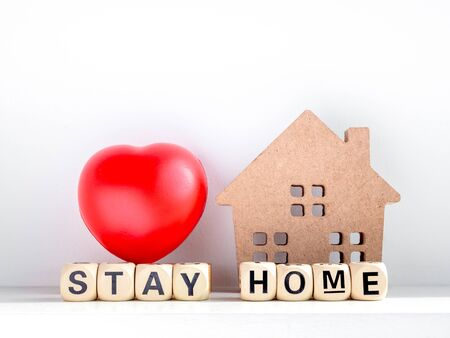 Stay home, stay safe concept. Stay home, words on wooden alphabet with small wooden home and red heart ball on white background.