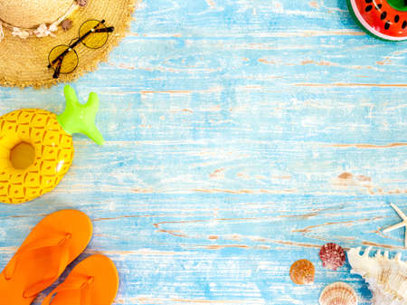 Colorful beach accessories, seashells, straw hat, sunglasses, orange flip flops and aerated beach ball on vintage blue wooden plank with space. Travel and vacation summer holiday background, top view.