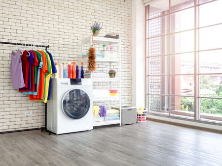 Laundry room interior. Utility room with washing machine, cleaning equipment, home cleaners, clean wipes, hanging colorful shirts on clothesline on white brick wall background near large glass window.
