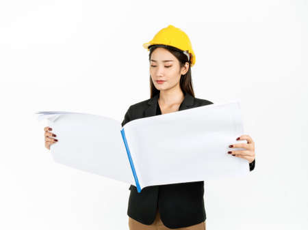 Young Asian businesswoman wearing black suit and yellow safety helmet checking project engineering paper plans in hands. Portrait of female engineer looking confident isolated on white background.