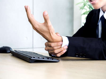 Close-up businessman in suit getting hand pain while using notebook computer in office. Suffering from work-related pain and office syndrome concept. Standard-Bild