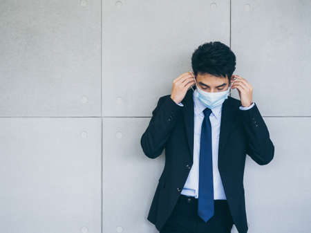 Young Asian businessman in suit wearing medical face mask on grey wall background in office with copy space, new normal working lifestyle after coronavirus pandemic lockdown. Banque d'images