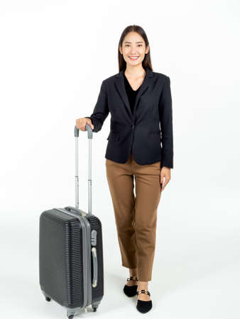 A young attractive Asian businesswoman in suit carrying her black suitcase on business trip and looking camera with smiling isolated on white background, vertical style.