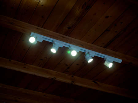 Modern LED Spotlights installed on wooden ceiling. Track lights rotatable lighting downlight glowing in the dark room.