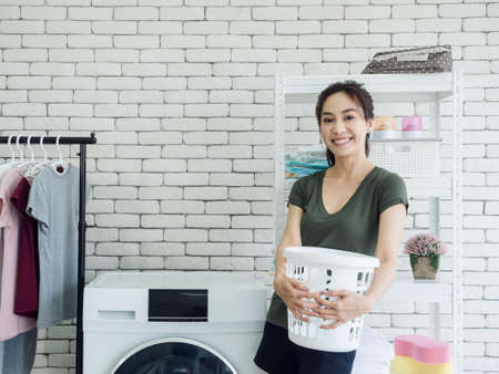 Beautiful young Asian woman housewife standing and holding empty white cloth basket with smiling near washing machine in laundry room. Reklamní fotografie