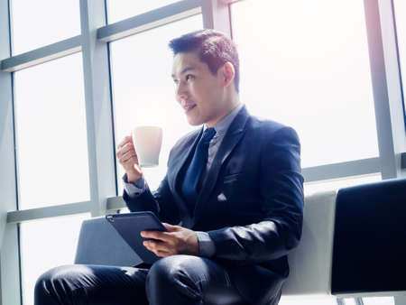 Good looking Asian businessman in suit holding tablet on his hand and drinking white cup of hot coffee while sitting on waiting chair near huge glass window with sunlight.