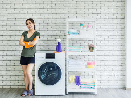 Beautiful smiling Asian woman, happy housewife wearing orange protective rubber gloves standing with arms folded beside washing machine on white brick wall background in bright clean laundry room.
