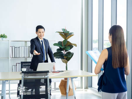 Asian businessman, boss in suit making hand gesture to invite young woman holding resume in the job interview to sit down on the chair near huge glass window in manager room in modern office interior.