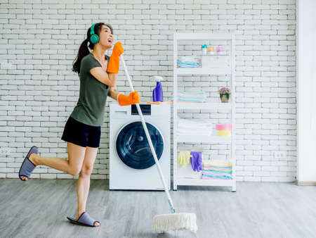 Happy beautiful young Asian woman, housewife wearing rubber gloves, slipper and green headphone singing fun with mop like a microphone while cleaning floor near wash machine on white wall background.
