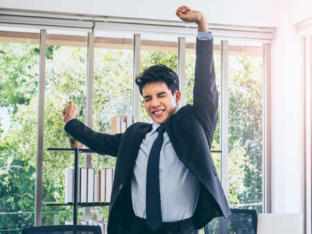 Young handsome Asian businessman in suit standing and stretching exercise near desk in office near huge glass window with sunlight.