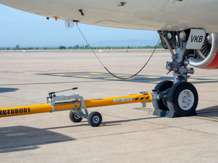 Khonkaen, Thailand - December 15, 2020 ; Airplane wheel with yellow pushing support equipment for trailers drove at Khonkaen Airport. Airplane parked at the airport and preparation for flight. Redakční