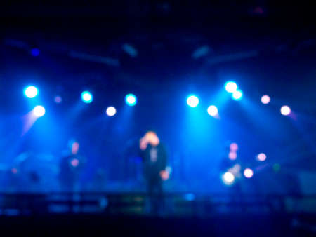 Blurred rock concert performing on stage with musician with blue light on dark background. Blurry music performance in rock band concert.