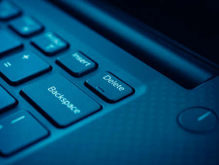 Delete key on black keyboard of laptop computer. Close up small embossed on delete button. Stock Photo