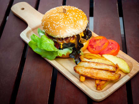 Delicious fresh homemade burger set. Tasty homemade hamburgers with french fries and sliced tomatoes on tray or wood cutting board on wooden table. 스톡 콘텐츠