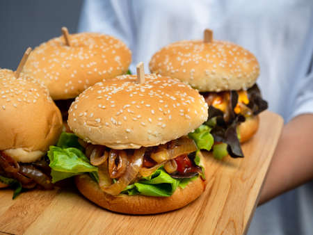 Delicious fresh homemade burger set. Woman wearing casual white t-shirt holding four tasty homemade hamburgers on wooden tray or wood cutting board on dark background.