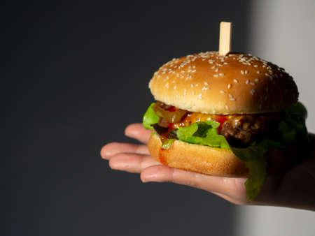 Delicious fresh homemade burger. hand holding tasty homemade hamburger on dark background. Hand showing beef burger.