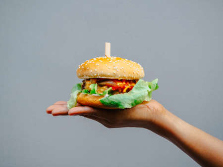 Delicious fresh homemade burger. hand holding tasty homemade hamburger isolated on grey background. Hand showing beef burger. 스톡 콘텐츠