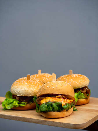 Delicious fresh homemade burger set. Hand holding and showing tasty four homemade hamburgers on wooden tray or wood cutting board on grey background with copy space, vertical style.