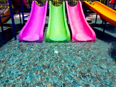 Colorful fun water slider in the pool with clear and clean water. 스톡 콘텐츠