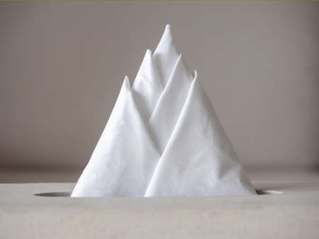 Close-up creative white clear tissue paper or napkins arranged in triangle mountain form in the box.