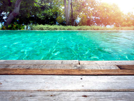 Old vintage style wood plank floor on poolside. Blank space on wooden floor near swimming pool with tree background, summer background concept.