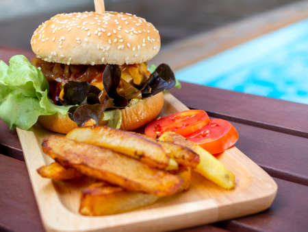 Delicious fresh homemade burger set. Tasty homemade hamburgers with french fries and sliced tomatoes on tray or wood cutting board on wooden table near swimming pool.
