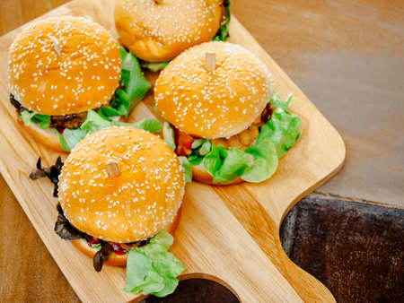 Delicious fresh homemade burger set. Four tasty homemade hamburgers on wooden tray or wood cutting board on dark background, top view. 스톡 콘텐츠