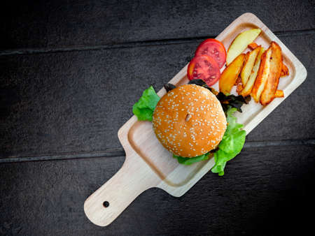 Delicious fresh homemade burger set. Top view of tasty homemade hamburgers with french fries and sliced tomatoes on tray or wood cutting board on dark wooden table with copy space.