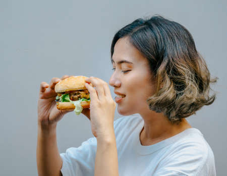 Delicious fresh homemade burger. Beautiful happy Asian woman short hair wearing casual white t-shirt holding and eating tasty homemade hamburger isolated on grey background.