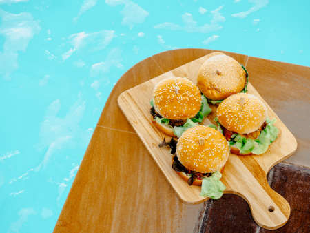 Delicious fresh homemade burger set. Four tasty homemade hamburgers on wooden tray or wood cutting board on dark background near the swimming pool.