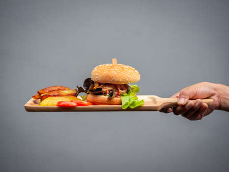 Delicious fresh homemade burger set. hand holding and showing tasty homemade hamburger with french fries and sliced tomatoes on wooden tray or wood cutting board.