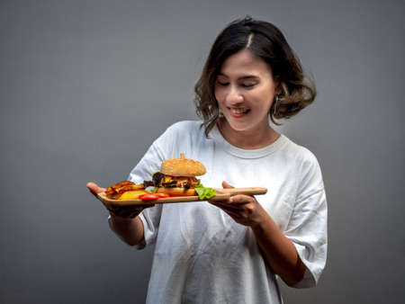 Delicious fresh homemade burger set. Beautiful Asian woman wearing casual white shirt holding tasty homemade hamburger with french fries and sliced tomatoes on wooden cutting board on dark background. 스톡 콘텐츠