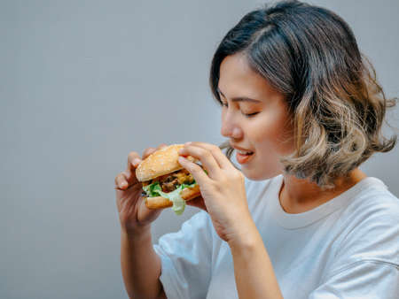 Delicious fresh homemade burger. Beautiful happy Asian woman short hair wearing casual white t-shirt holding and eating tasty homemade hamburger isolated on grey background with copy space.